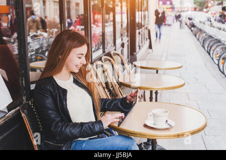 Young woman using digital tablet computer in street cafe en europe Banque D'Images