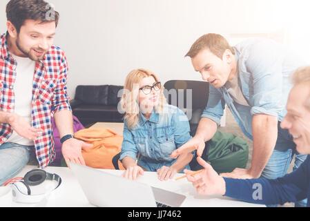 Collègues positifs à l'aide d'ordinateur portable dans le bureau Banque D'Images