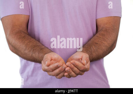 Mid section of man with hands cupped standing against white background Banque D'Images