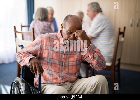 Déprimé mobilité senior man sitting on fauteuil roulant à maison de retraite Banque D'Images
