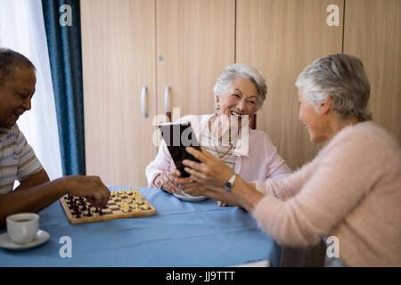 Smiling friends jouant aux échecs et l'utilisation de la technologie tout en étant assis à table dans la maison de soins infirmiers