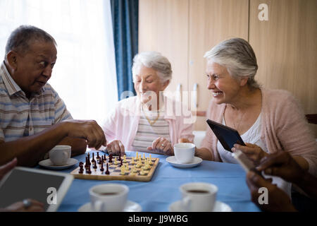 Happy friends jouant aux échecs tandis que le café à table dans la maison de soins infirmiers