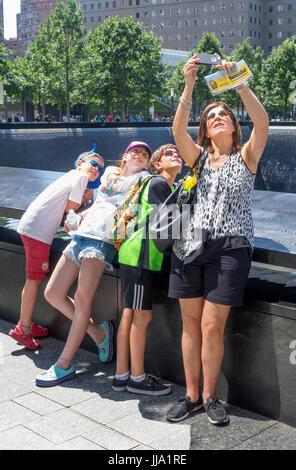 Mère de prendre une famille avec ses trois enfants selfies à la piscine du sud de World Trade Center à New York Banque D'Images