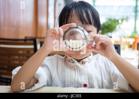 Chinois asiatique peu girl drinking beverage at outdoor restaurant Banque D'Images