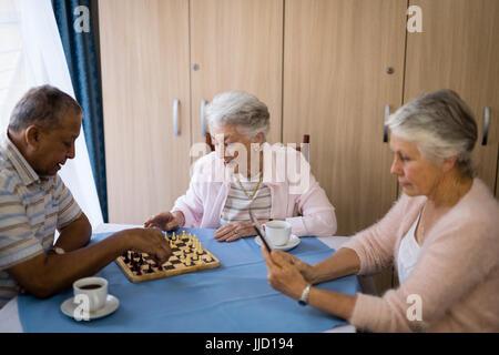 Senior friends jouant aux échecs et le café tout en étant assis à table dans la maison de soins infirmiers