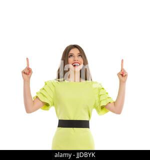 Jeune femme en robe verte à la chaux et de pointage. Waist up studio shot isolé sur blanc.