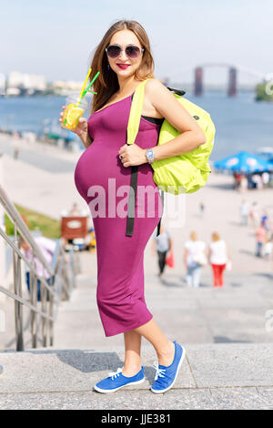 Jolie jeune femme enceinte boire du jus et profiter de sa balade sur le remblai de la ville. Touriste, active et Banque D'Images
