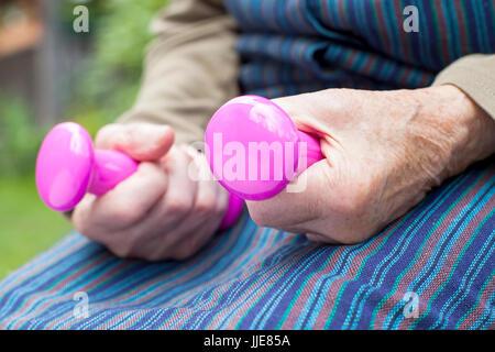 Close up photo de personnes âgées woman's hands holding dumbbells rose à l'extérieur Banque D'Images