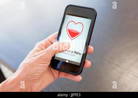 Devenir un héros du texte avec forme de coeur à l'écran contre l'image recadrée de hand holding smart phone Banque D'Images