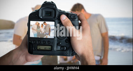 Portrait of hands holding camera cheerful young friends having barbecue together Banque D'Images