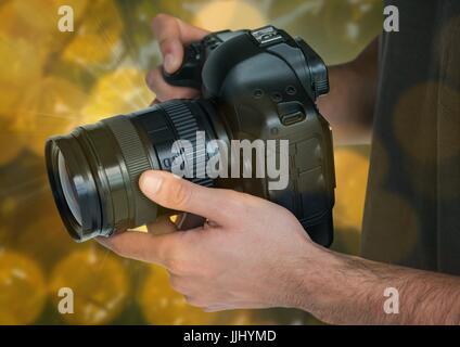 Appareil photo de photographe les mains. Arrière-plan flou vert et jaune et se chevauchent. Banque D'Images