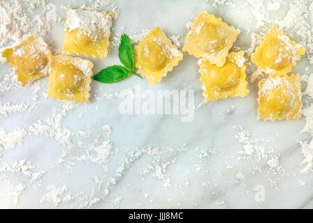 Une photo prise à la verticale de ravioli avec la farine et les feuilles de basilic, tourné à partir de ci-dessus Banque D'Images