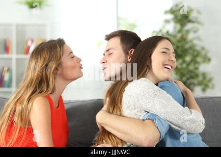 La tricherie garçon à sa petite amie avec sa meilleure amie assise sur un sofa à la maison Banque D'Images