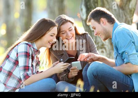 Trois adolescents à la ligne de partage de contenu sur leurs téléphones intelligents assis sur l'herbe dans un parc Banque D'Images
