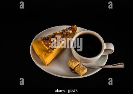 Aromatiques du café noir en blanc tasse avec soucoupe, blanc gâteau au fromage sur le sucre brun, cuillère à café, Banque D'Images