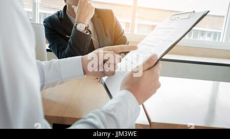 L'homme d'affaires à l'intervieweur sceptique pendant l'écoute d'une femme d'origine asiatique interview Banque D'Images