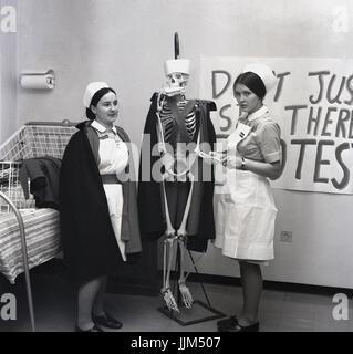 """""""Est-il encore en vie?"""" des années 60, en Angleterre, sur un hôpital, deux femmes en soins infirmiers avec un modèle grandeur nature avec un squelette habillé nurse's cape et chapeau et un sandwich dans sa bouche. Une des infirmières a fait semblant de vérifier le pouls du squelette dans une protestation à propos de survivre sur les bas salaires."""