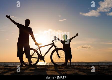 Père et fils jouant sur la plage, à l'heure du coucher du soleil. Notion de plaisir familial. Banque D'Images