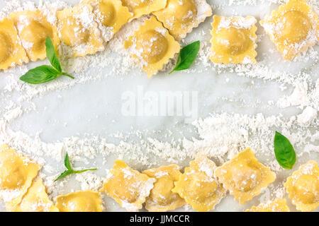 Photo prise à la verticale de ravioli avec la farine et les feuilles de basilic Banque D'Images