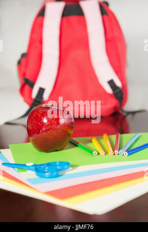 Apple et les fournitures scolaires avec sac à dos rouge en arrière-plan Banque D'Images