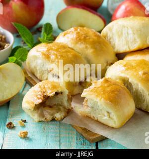 Des tartes aux pommes avec des pommes fraîches et de noix de la pâte sur une table de bois de cuisine. Galettes Banque D'Images
