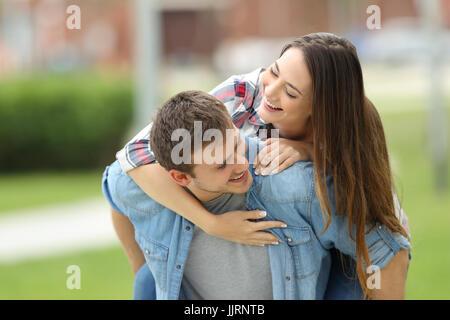 Vue de face d'un couple d'adolescents plaisanter ensemble piggyback en plein air dans un parc avec un fond vert Banque D'Images