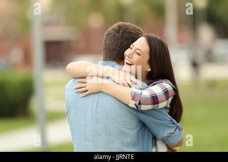 Heureuse rencontre de deux friends hugging outdoors in a park Banque D'Images