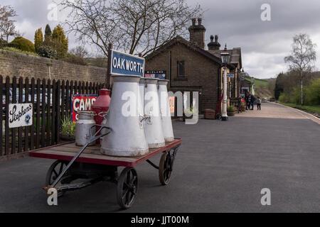 Voir de vieux bidons de lait & annonces sur le panier, sur la plate-forme à l'endroit calme et pittoresque, historique Oakworth Station - Keighley et vaut Valley Railway, England, UK.