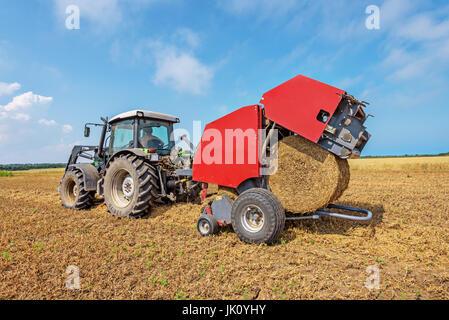 Le tracteur dans un champ avec des balles de paille.