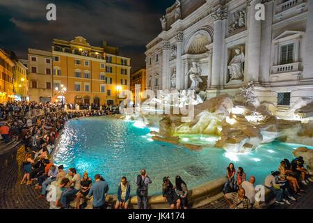 La fontaine de Trevi à Rome Italie colorée et éclairée le soir avec les touristes qui l'entoure sur une chaude soirée Banque D'Images