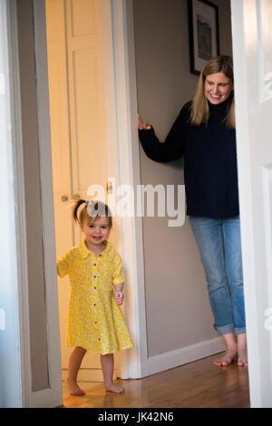Mère regardant Caucasian baby daughter standing in doorway Banque D'Images