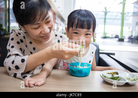 Chinois asiatique mother and daughter eating beef nouilles dans outdoor cafe Banque D'Images