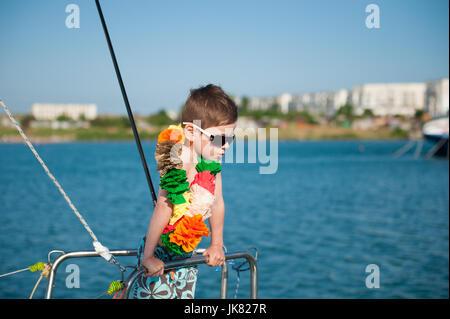 Cute little boy wearing sunglasses et décoration hawaïenne sur le cou à bord d'un bateau de plaisance Banque D'Images