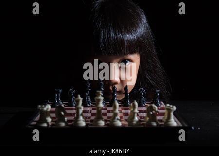 Petite fille asiatique chinois jouant aux échecs dans l'arrière-plan noir isolé