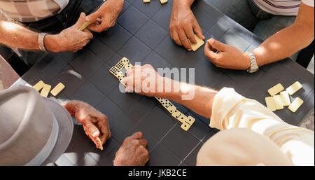 Les retraités, les personnes âgées et temps libre. Vieux hommes latino s'amusant et en jouant le jeu de domino à Banque D'Images