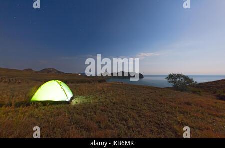 Tourist tente sur un promontoire près de la mer sur le fond du ciel nocturne. Le concept de voyager avec des tentes Banque D'Images