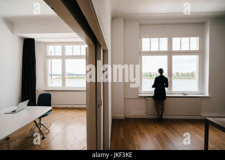 Businesswoman in office looking out of window Banque D'Images