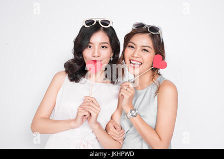 Deux femmes à la mode dans de jolies robes Standing together and holding red heart shape. Banque D'Images