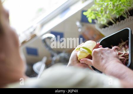Senior woman peeling pommes de terre rouges, la préparation des aliments. L'orientation horizontale avec focus sélectif Banque D'Images