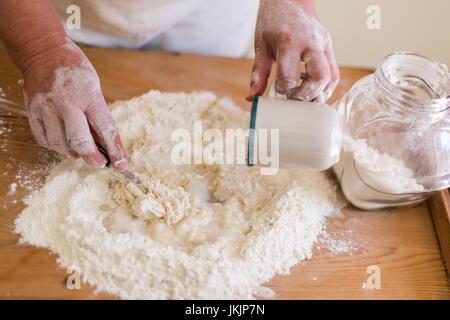 Hauts femme fait à l'aide de pâte de farine et verser de l'eau. Vue de dessus, selective focus on travaillant avec Banque D'Images