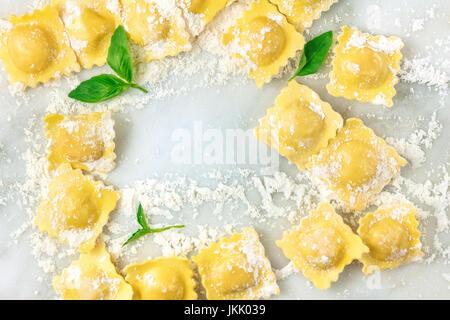 Une photo prise à la verticale de ravioli avec la farine et les feuilles de basilic, formant un cadre, tourné à Banque D'Images