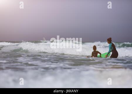 Athletic Girl avec petit garçon lui apprendre le surf Banque D'Images