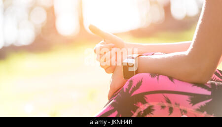 Anonyme attrayant sportive woman wearing smart watch showing Thumbs up après séance d'entraînement Banque D'Images