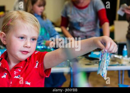 Portrait enfant blonde, fille, 5-6 ans, tenant à l'écart de elle-même, à bout de bras, un morceau de papier d'aluminium Banque D'Images