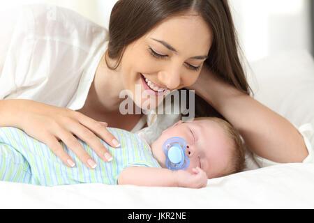 Fière maman de regarder son bébé dormir sur un lit à la maison Banque D'Images