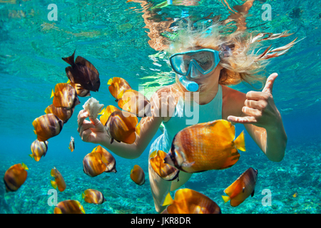 Happy Family - girl à la plongée sous-marine plongée masque avec les poissons tropicaux dans la mer de corail Extérieure. Banque D'Images