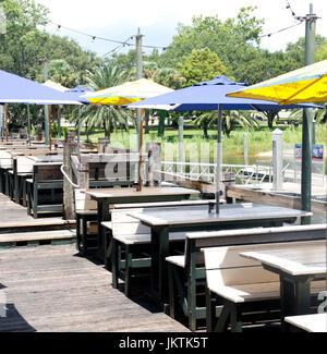 Vue d'un restaurant en plein air sur le front de mer. Il y a des sièges couverts de table de pique-nique en bois en bleu et jaune de parasols. Banque D'Images