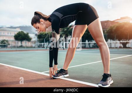 Beautiful young girl doing stretching workout extérieur. Grande sportive faisant l'exercice d'échauffement sur un Banque D'Images