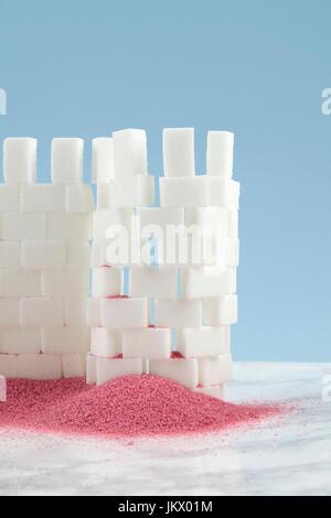 Un château construit avec cube de sucre et de sable rose à ses pieds. Minime et conception drôle still life la photographie. Banque D'Images