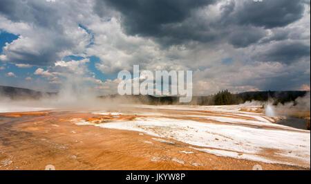 Piscine arc-en-ciel Hot spring run off passé la falaise Geyser en fer Spring Creek dans le bassin de sable noir Banque D'Images